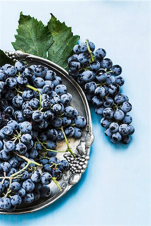 Blue grapes on a metal plate and next to it Stock Photo - Premium Royalty-Free, Code: 659-07959694