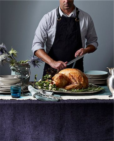 A man carving a roast turkey Stock Photo - Premium Royalty-Free, Code: 659-07959721