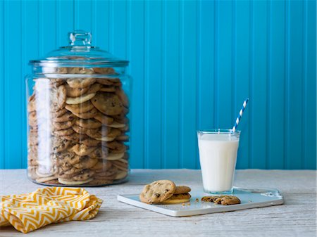 A giant cookie jar filled with chocolate chip cookies with a plate of cookies and milk in the foreground Stock Photo - Premium Royalty-Free, Code: 659-08147041