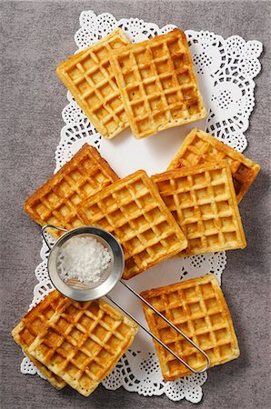dessert - Waffles and a sieve of icing sugar on a doily Stock Photo - Premium Royalty-Free, Code: 659-08147076