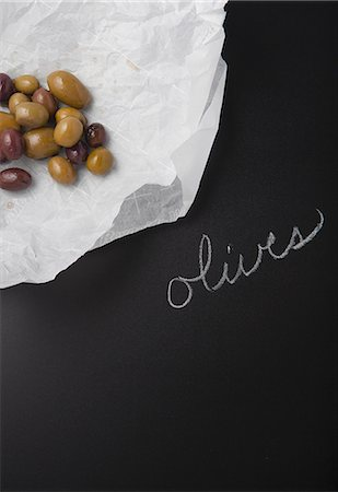 descriptive - Olives on a piece of paper on a slate surface with a label Stock Photo - Premium Royalty-Free, Code: 659-08147216