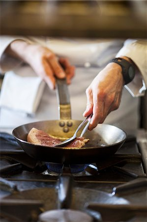 A chef preparing a steak in a commercial kitchen Stock Photo - Premium Royalty-Free, Code: 659-08147604