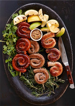 Sausage skewers with lemons on a bed of herbs Stock Photo - Premium Royalty-Free, Code: 659-08420120