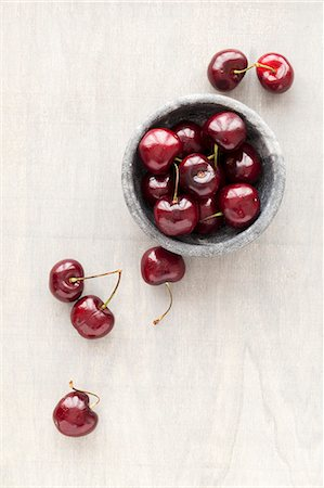 Fresh cherries in a marbled bowl and next to it Stock Photo - Premium Royalty-Free, Code: 659-08513050