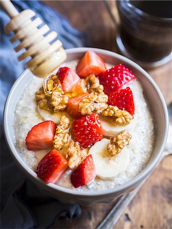 Healthy breakfast: oatmeal porigge with coco, chia seeds, nuts, fresh fruit and honey Stock Photo - Premium Royalty-Free, Code: 659-08897314