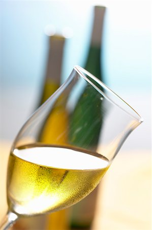 Glass of white wine, held at an angle, in front of two bottles Stock Photo - Premium Royalty-Free, Code: 659-01844229