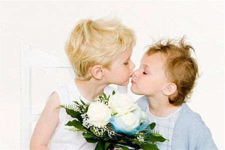 Two children kissing over a bouquet of white roses Stock Photo - Premium Royalty-Free, Code: 659-01855587