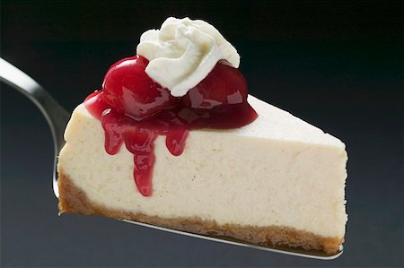Slice of cheesecake with cherries and cream on cake server Stock Photo - Premium Royalty-Free, Code: 659-01857939