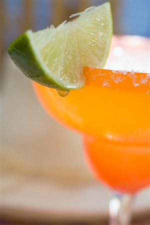 Margarita with wedge of lime in orange glass Stock Photo - Premium Royalty-Free, Code: 659-01858652