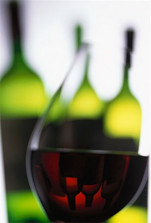 Glass of red wine in front of wine bottles Stock Photo - Premium Royalty-Free, Code: 659-01850062