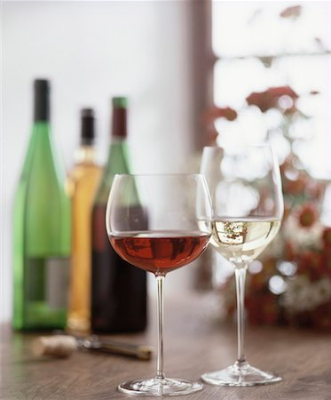 Glasses of red and white wine, wine bottles in background Stock Photo - Premium Royalty-Free, Code: 659-01850073
