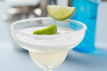 Margarita with lime wedges in a glass with a salted rim Stock Photo - Premium Royalty-Free, Code: 659-02212401