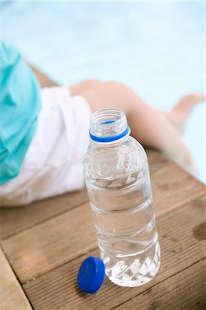 Child sitting beside bottle of water on edge of pool Stock Photo - Premium Royalty-Free, Code: 659-03524301