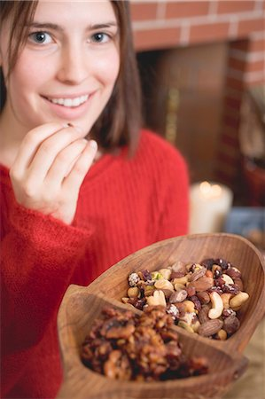 sweater and fireplace - Young woman eating nuts in front of fireplace (Christmas) Stock Photo - Premium Royalty-Free, Code: 659-03525105