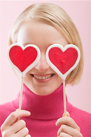 picture of a red lollipop - Love is blind: woman with heart-shaped lollipops in front of her eyes Stock Photo - Premium Royalty-Free, Code: 659-03521769