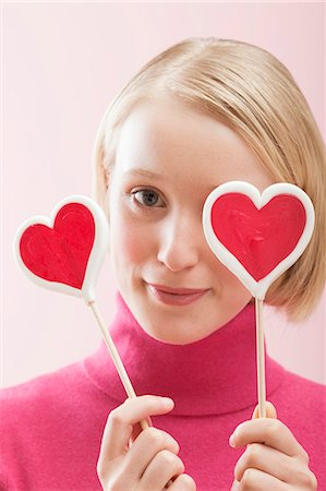 picture of a red lollipop - Young woman with heart-shaped lollipops in front of her eyes Stock Photo - Premium Royalty-Free, Code: 659-03521770
