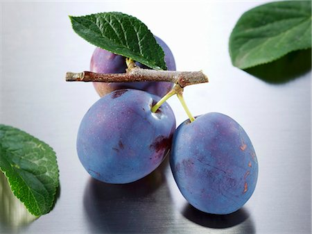 Plums (variety: Hanita) with twig and leaf Stock Photo - Premium Royalty-Free, Code: 659-03535674