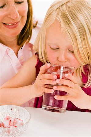 Girl drinking water with raspberry ice cubes Stock Photo - Premium Royalty-Free, Code: 659-03536934