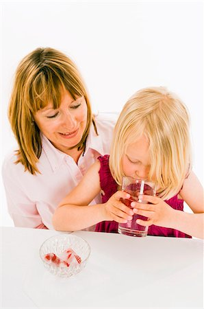 Girl drinking water with raspberry ice cubes Stock Photo - Premium Royalty-Free, Code: 659-03536935