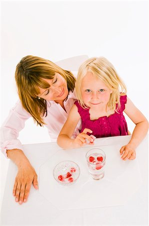 Mother and daughter, daughter holding a raspberry ice cube Stock Photo - Premium Royalty-Free, Code: 659-03536936