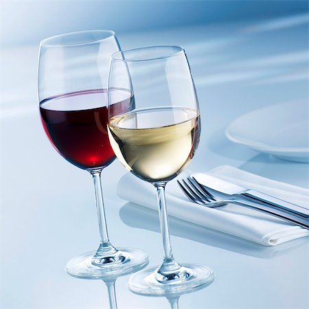 Glass of white wine and glass of red wine beside place-setting Stock Photo - Premium Royalty-Free, Code: 659-03537621