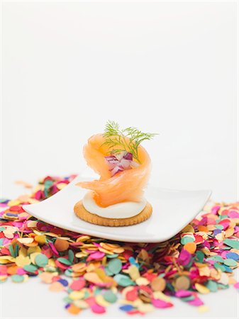 Smoked salmon on cracker on plate surrounded by confetti Stock Photo - Premium Royalty-Free, Code: 659-03531015