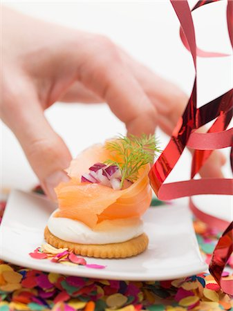 Hand reaching for cracker topped with smoked salmon Stock Photo - Premium Royalty-Free, Code: 659-03531016