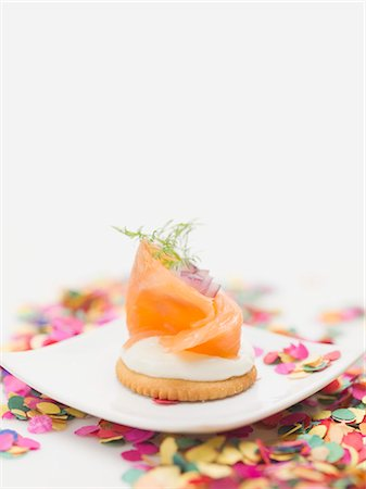 Smoked salmon on cracker on plate surrounded by confetti Stock Photo - Premium Royalty-Free, Code: 659-03531018