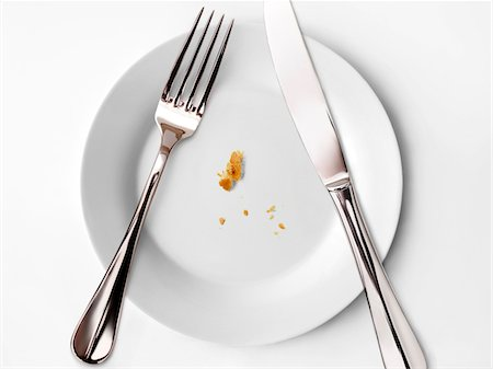 Crumbs on a plate,knife and fork Stock Photo - Premium Royalty-Free, Code: 652-05808225