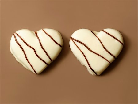 Heart-shaped white chocolate biscuits Stock Photo - Premium Royalty-Free, Code: 652-05808883