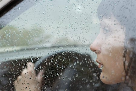 A woman driver sitting in car looking out window, raindrops on window Stock Photo - Premium Royalty-Free, Code: 653-05393209