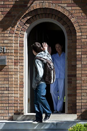 Son and Mother waving goodbye to each other at front door as son leaves house Stock Photo - Premium Royalty-Free, Code: 653-05393266