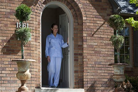 Smiling woman wearing Pajamas leans on front door and looks out Stock Photo - Premium Royalty-Free, Code: 653-05393275