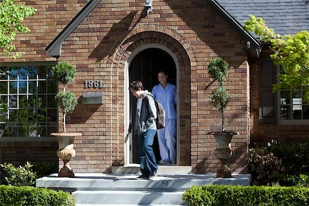 Smiling Mother stands at front door of house as son departs Stock Photo - Premium Royalty-Free, Code: 653-05393270