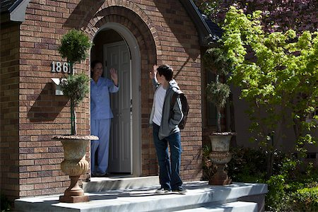 Son and Mother waving goodbye to each other at their front door as son leaves house Stock Photo - Premium Royalty-Free, Code: 653-05393273