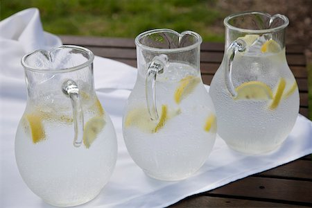 Three pitchers of ice water with lemon slices Stock Photo - Premium Royalty-Free, Code: 653-05393322