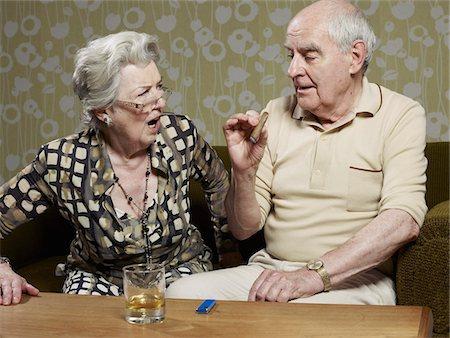 Senior woman looks shocked as senior man smokes cigar Stock Photo - Premium Royalty-Free, Code: 653-05393366