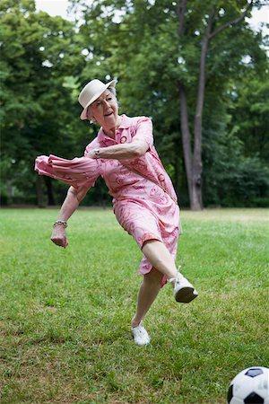Senior woman kicks football n the park Stock Photo - Premium Royalty-Free, Code: 653-05393376