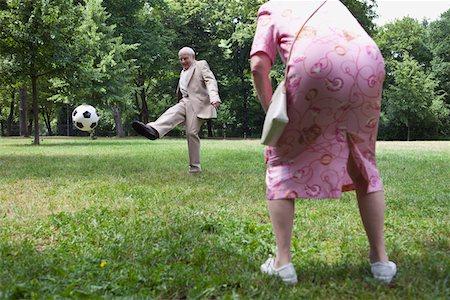 Senior couple play football in the park Stock Photo - Premium Royalty-Free, Code: 653-05393377