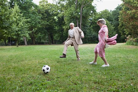 Senior man and woman play football in the park Stock Photo - Premium Royalty-Free, Code: 653-05393379