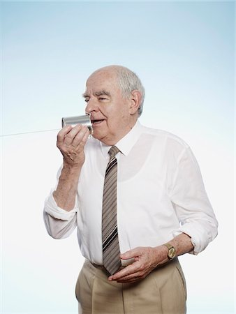 string - Senior man speaks into tin can phone Stock Photo - Premium Royalty-Free, Code: 653-05393385