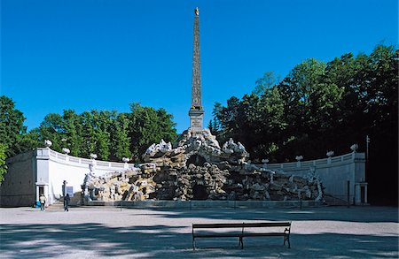 Austria, Vienna, Obelisk fountain at Schonbrunn palace with empty bench in the foreground Stock Photo - Premium Royalty-Free, Code: 653-05393415