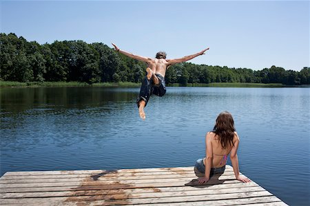 summer - Guy dives into lake with arms outstretched as girl watches on jetty Stock Photo - Premium Royalty-Free, Code: 653-05393444