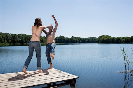 pushing - Girl on jetty pushes guy into water Stock Photo - Premium Royalty-Free, Code: 653-05393452