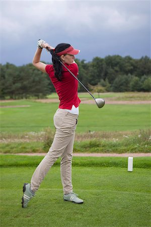 A female golfer teeing off Stock Photo - Premium Royalty-Free, Code: 653-05855436