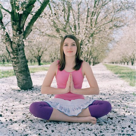 A girl practicing yoga in the lotus position Stock Photo - Premium Royalty-Free, Code: 653-05855474
