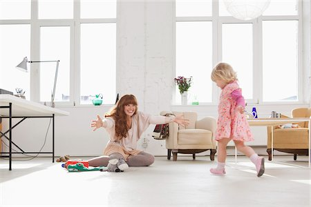 A young girl running towards her mother sitting on the floor Stock Photo - Premium Royalty-Free, Code: 653-05855504