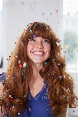 A smiling woman looking up at confetti falling Stock Photo - Premium Royalty-Free, Code: 653-05855522