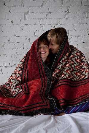 A young happy couple wrapped in a blanket Stock Photo - Premium Royalty-Free, Code: 653-05855523