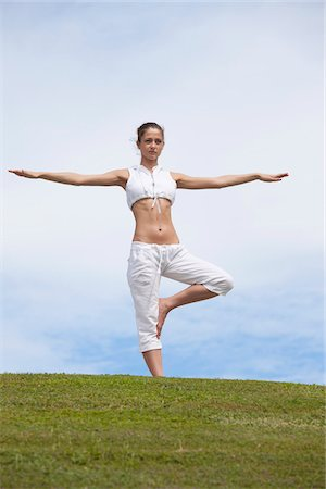practise - Girl does yoga pose on hillside Stock Photo - Premium Royalty-Free, Code: 653-05975950